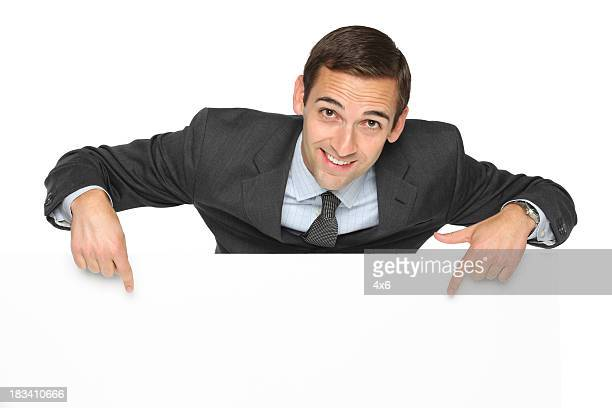 Smiling businessman pointing at blank sign
