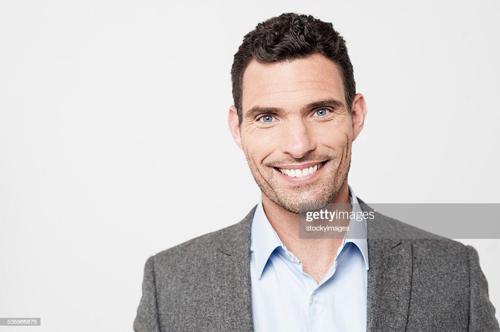 Smiling businessman posing to camera : Stock Photo
