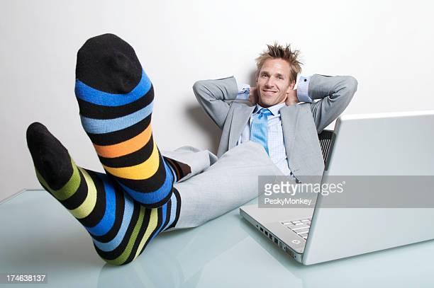 Sorridente Uomo d'affari rilassanti con i piedi fino alla scrivania