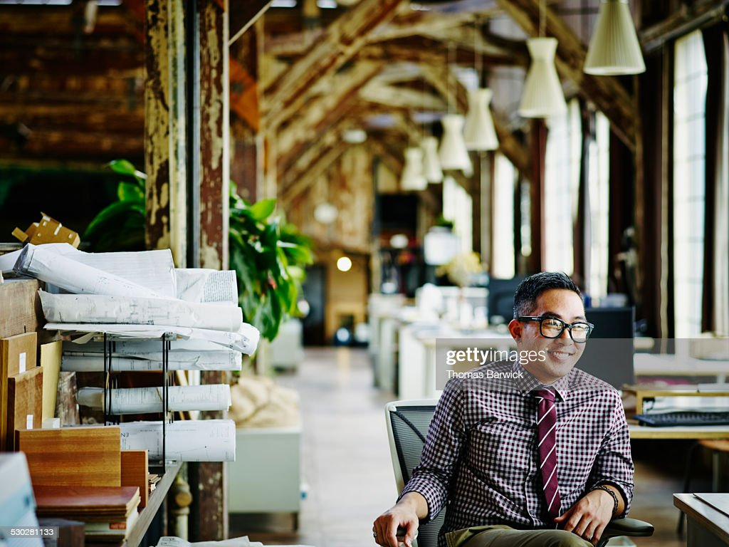 Smiling businessman seated in design office
