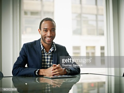 Smiling businessman sitting at conference table : Photo