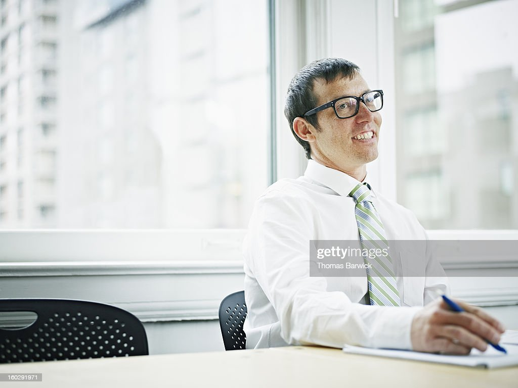 Smiling businessman sitting at conference table : Stock Photo