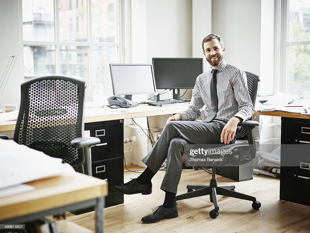 Smiling businessman sitting at workstation : Stock Photo