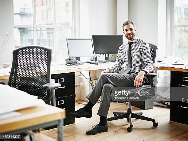 Smiling businessman sitting at workstation