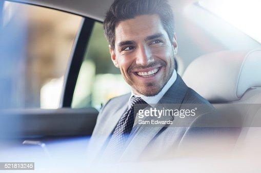 Smiling businessman sitting in car