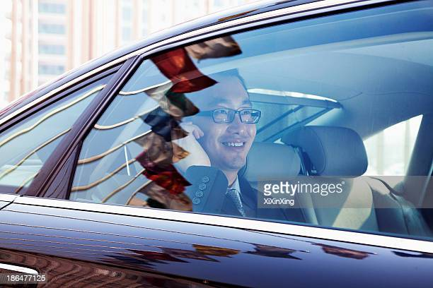 Smiling Businessman sitting in the back seat of the car