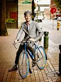 Smiling businessman sitting on bicycle on sidewalk