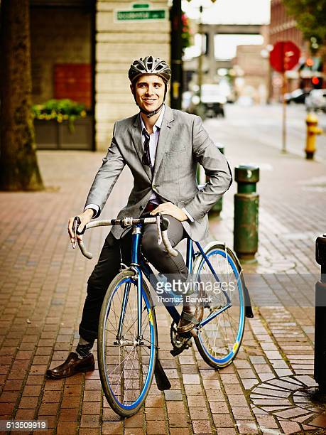 Smiling businessman sitting on bicycle on sidewalk