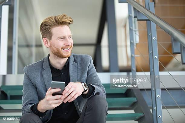 Lächelnd Geschäftsmann sitzen auf der Treppe hält seine Mobiltelefon.
