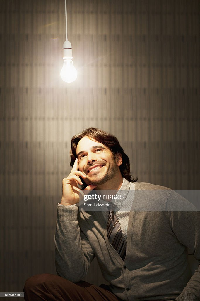 Smiling businessman sitting under illuminated light bulb : ストックフォト
