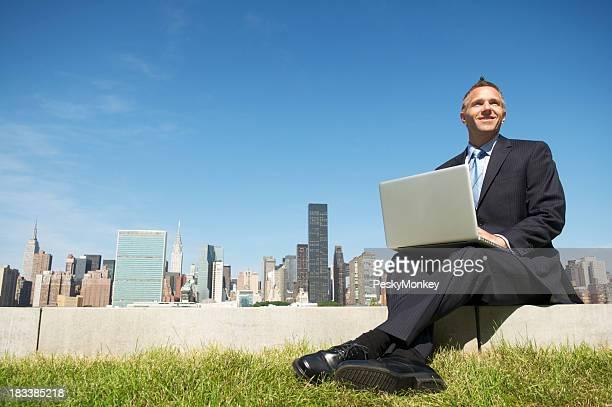 Lächelnd Geschäftsmann sitzt mit Laptop im Freien mit Blick auf die Skyline der Stadt