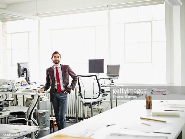 Smiling businessman standing at workstation