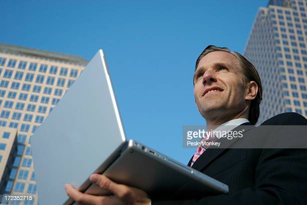 Smiling Businessman Standing City Skyline Outside with Laptop