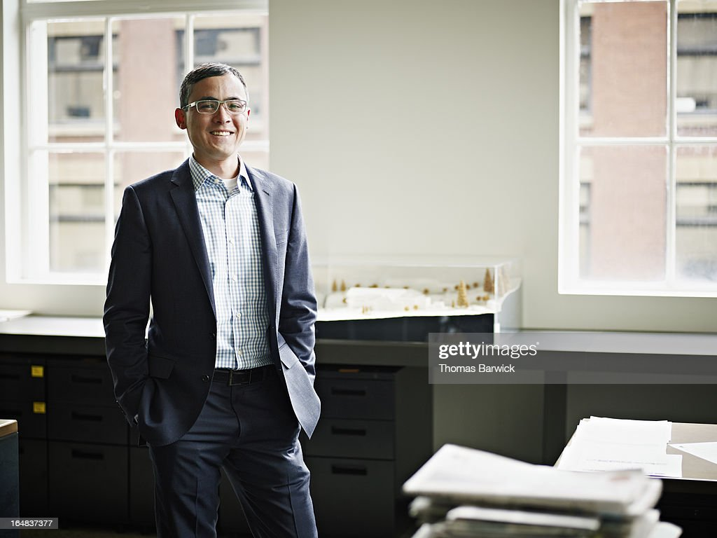 Smiling businessman standing in architects office : Stock Photo
