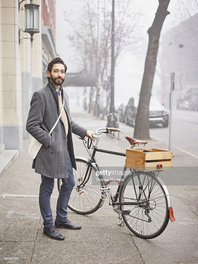 Smiling businessman standing next to bike