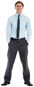 Smiling businessman standing with hands in pockets on white background
