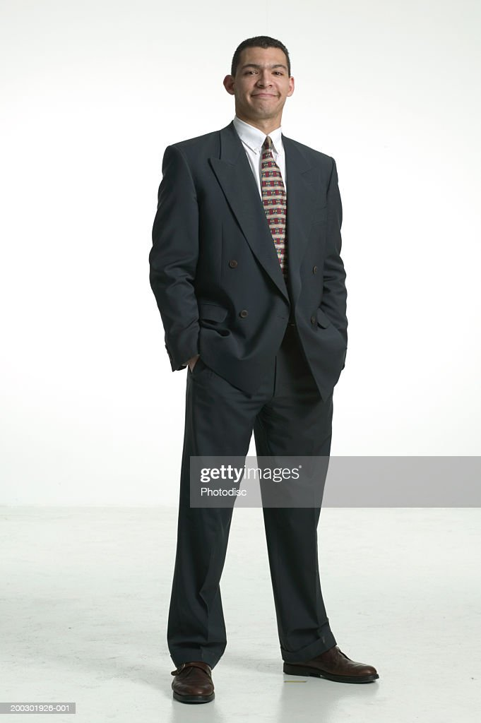 Smiling businessman standing with hands in pockets, portrait : Stock Photo