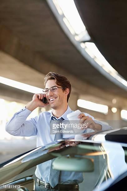 笑顔で話しているビジネスマンが携帯電話やコーヒーカップを手