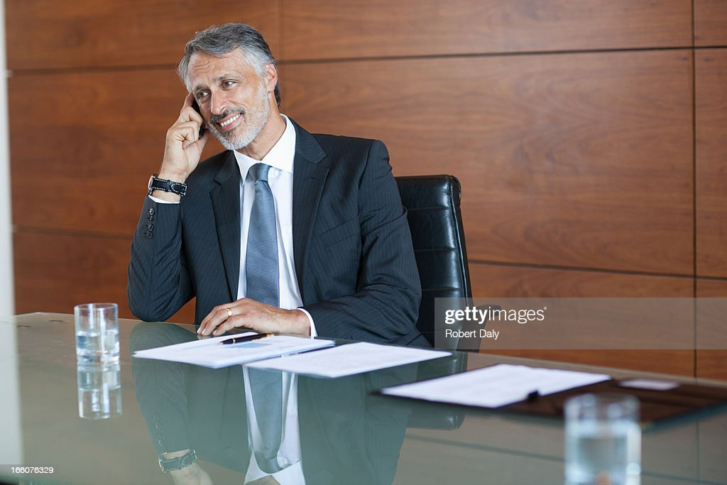 Smiling businessman talking on cell phone in conference room : Stock Photo