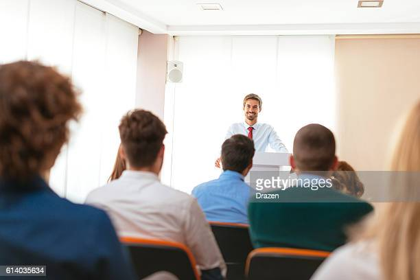 Smiling businessman talks to attendees in symposium