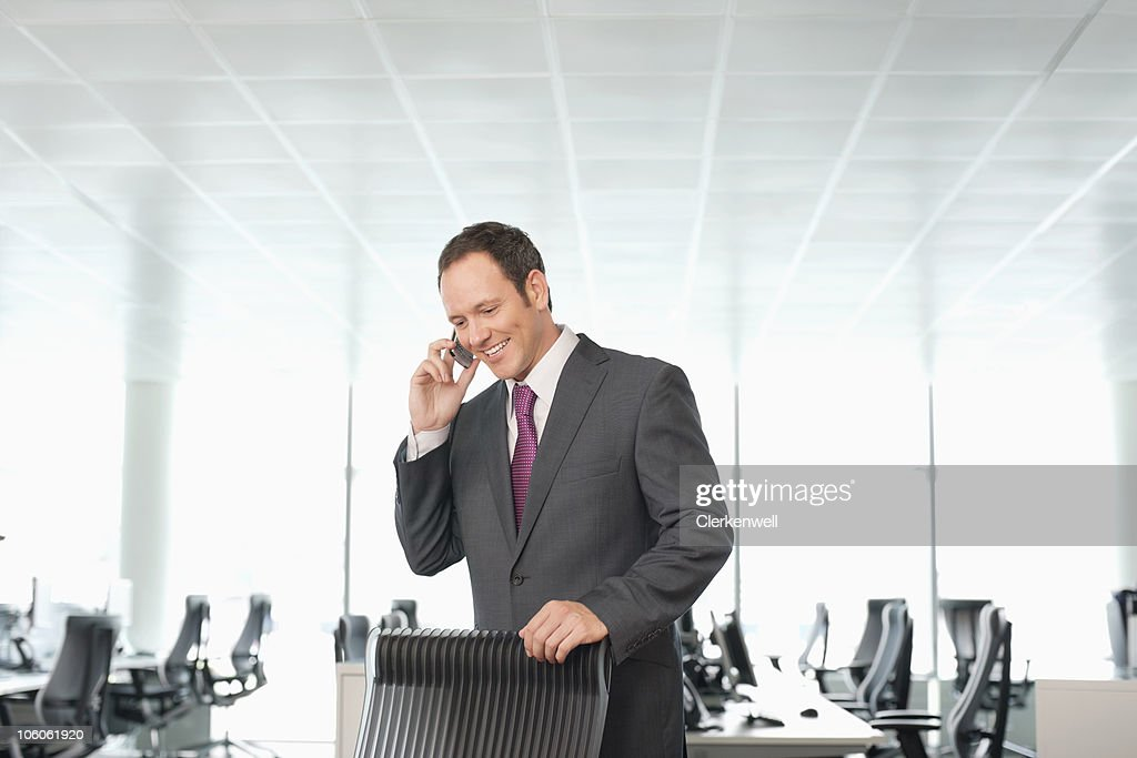 Smiling businessman using a mobile phone at office : Stock Photo