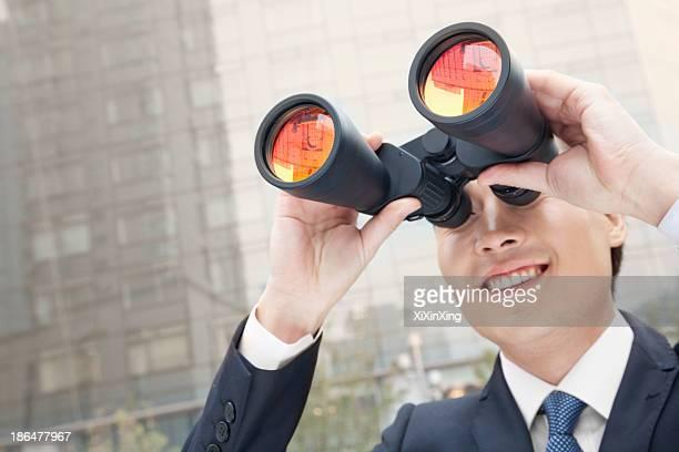 Smiling Businessman Using Binoculars, Reflection