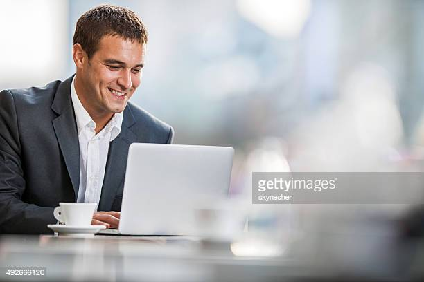 Smiling businessman using computer on a break in a cafe.