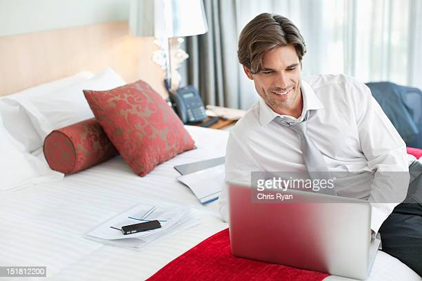 Smiling businessman using laptop on bed in hotel room