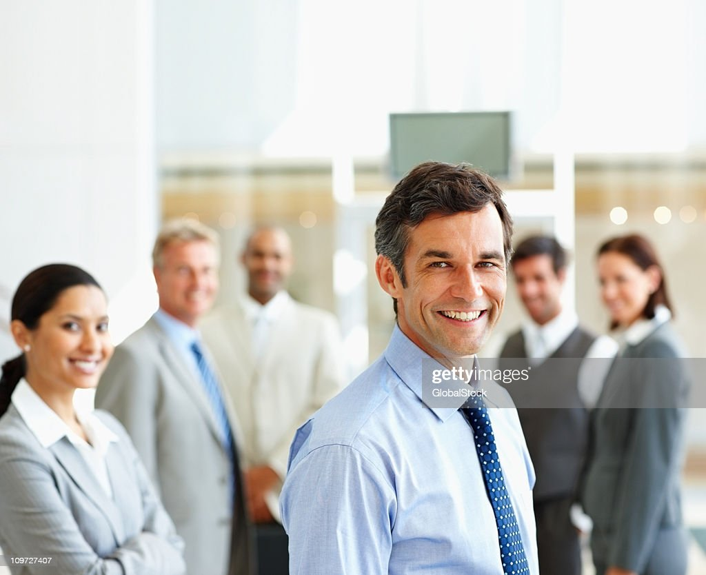 Smiling businessman with colleagues in the background : Stock Photo