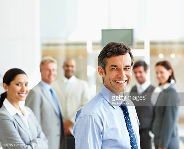 Smiling businessman with colleagues in the background