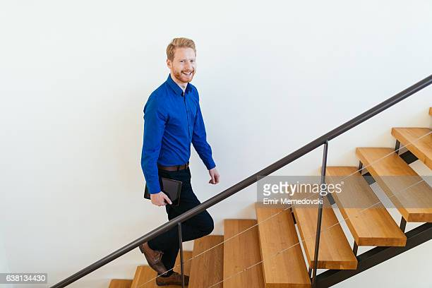 Smiling businessman with digital tablet climbing staircase