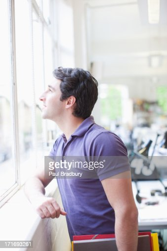 Smiling businessman with folders looking out office window : Stock Photo