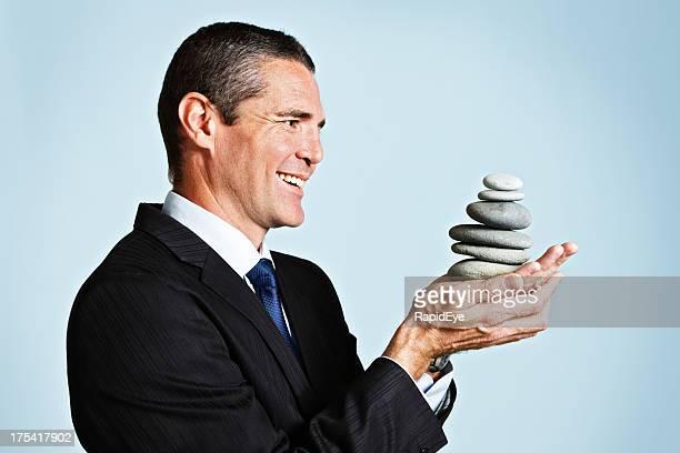 Uomo d'affari sorridente con pietre Zen contro il cielo-sfondo blu