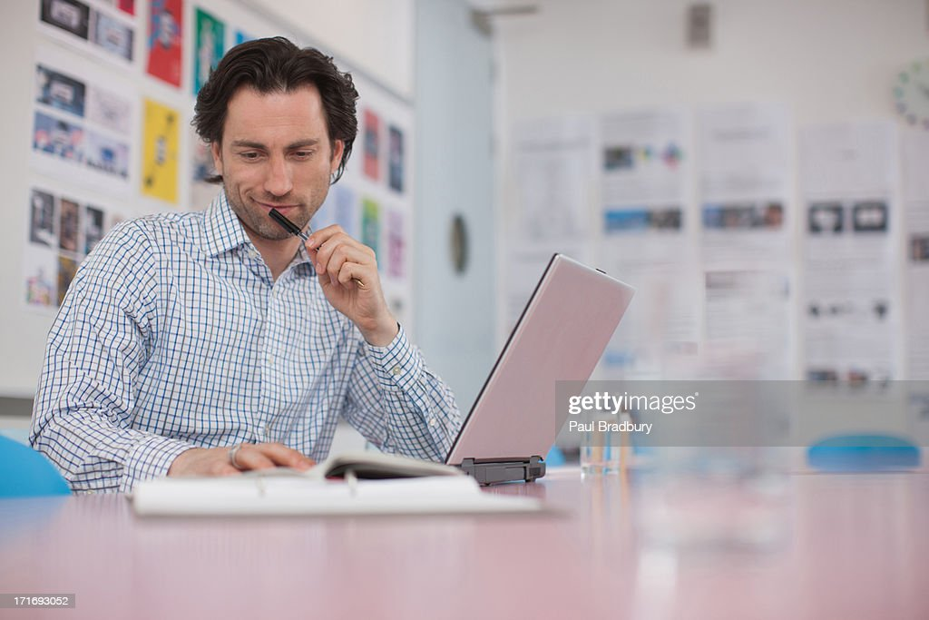 Smiling businessman working at laptop in office : Stock Photo