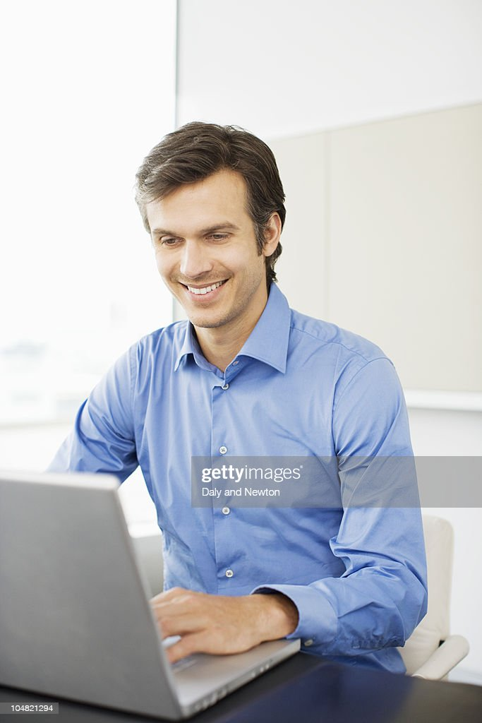 Smiling businessman working at laptop : Stock Photo