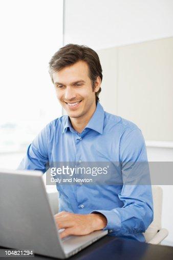 Smiling businessman working at laptop : Stock Photo