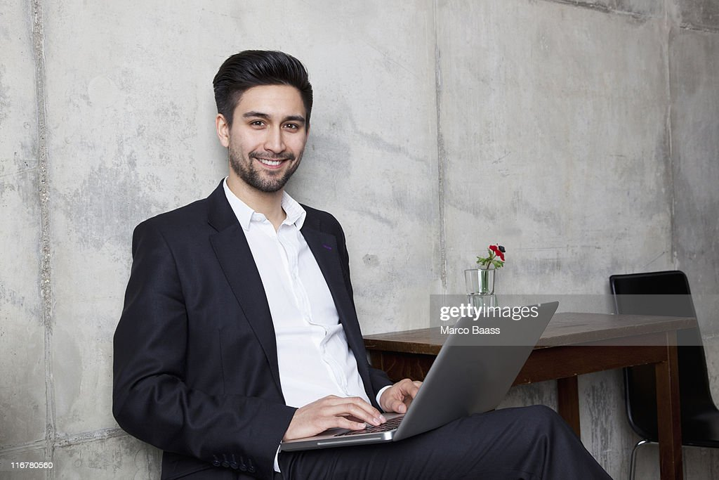A smiling businessman working on a laptop