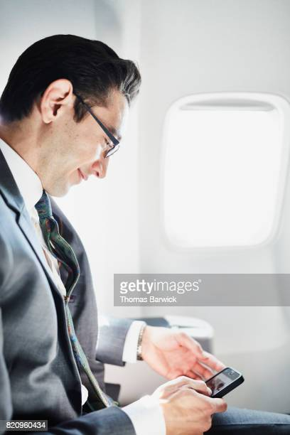 Smiling businessman working on smartphone while traveling on business trip on airplane