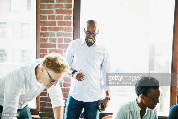Smiling businessman working with colleagues on project in office conference room