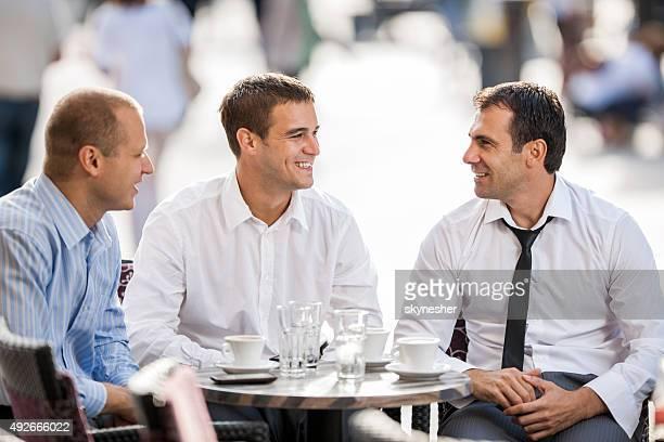 Lächelnde Geschäftsleute Kommunikation auf eine Pause in einem Café.