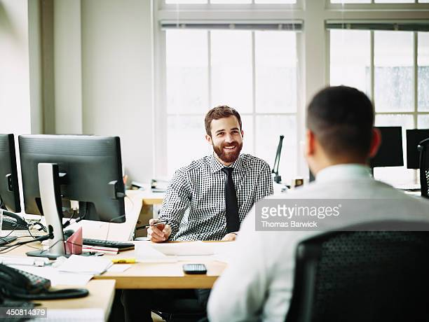 Smiling businessmen in discussion in office