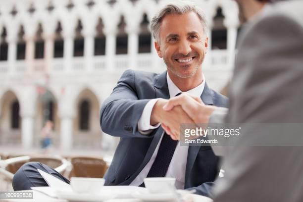 Smiling businessmen shaking hands at sidewalk cafe