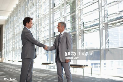 Smiling businessmen shaking hands in modern lobby : Stock Photo