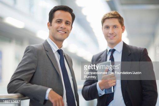 Smiling businessmen standing in office corridor
