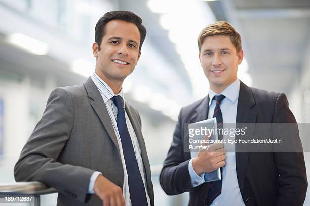 Smiling businessmen standing in office corridor