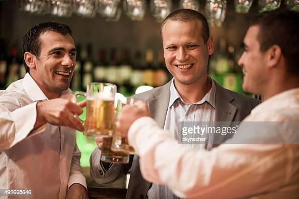 Lächelnd Geschäftsmann Anstoßen mit Bier in der bar.