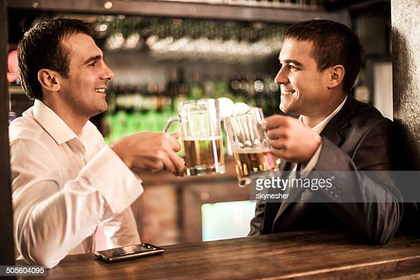 Smiling businessmen toasting with beer.