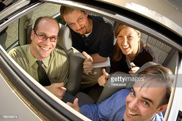 Smiling businesspeople inside car