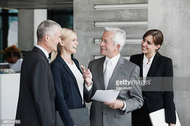 Smiling businesspeople talking in office
