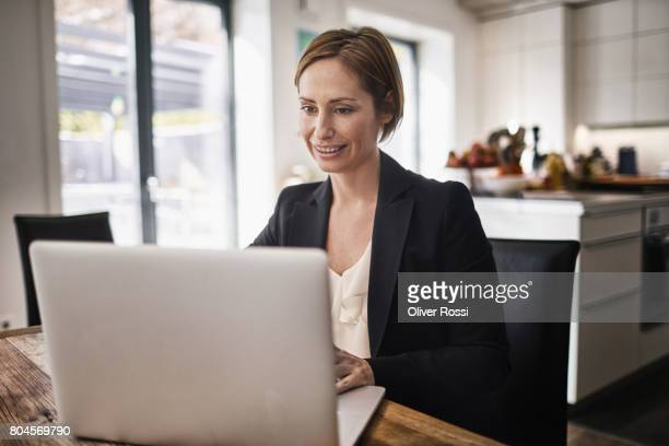 Smiling businesswoman at home using laptop